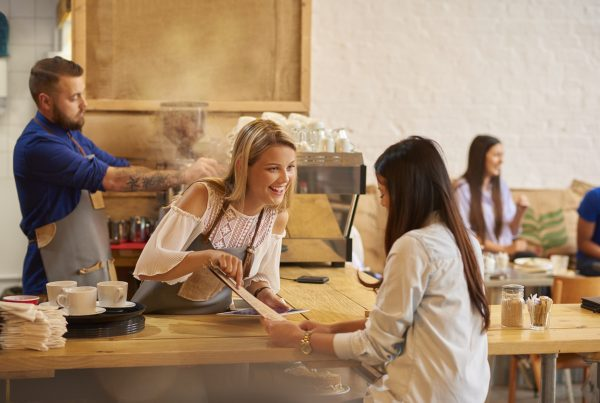 a coffee shop worker smiles at the customer as she recommends her favourite thing on the menu . In the background a male colleague is making coffee and other customers can be seen having fun